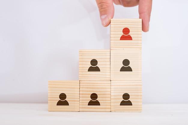 Conceito de negócio de recrutamento e gestão de recursos humanos, mão colocando bloco de cubo de madeira no topo da pirâmide, espaço para texto