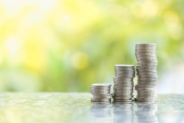Conceito de negócio, dinheiro, economia e segurança. feche acima de três pilhas instáveis de moedas com bokeh da natureza verde da folha.