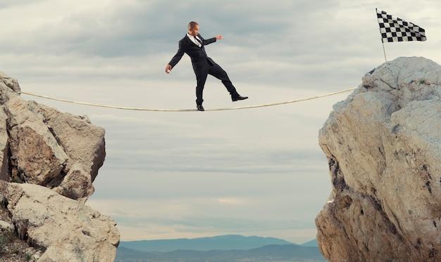 Conceito de negócio do empresário que supera os problemas para chegar à linha de chegada em uma corda
