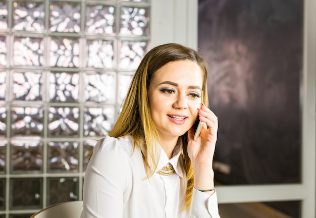 Conceito de negócio - empresária falando ao telefone no escritório