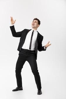 Conceito de negócio - empresário alegre e bonito, mostrando as mãos no ar sobre fundo cinza.