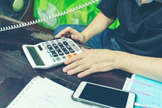 Conceito de negócio: empresário local no telefone e usando a calculadora no escritório