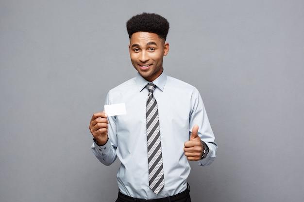 Conceito de negócio - feliz bonito empresário americano africano mostrando o cartão de visita para o cliente.