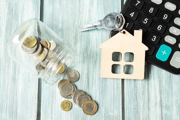Conceito de negócio, finanças, poupança, escada de propriedade ou empréstimo hipotecário: modo de casa de madeira, moedas espalhadas do frasco de vidro, calculadora.