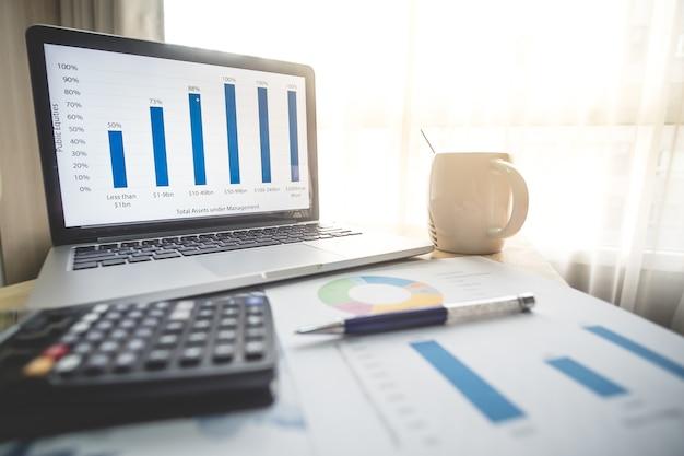Conceito de negócio financeiro laptop, caneta, café, gráfico para finanças, negócios na mesa
