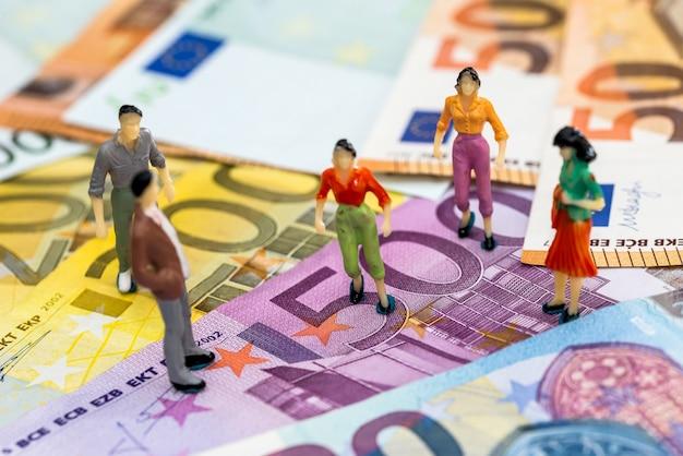 Conceito de negócio financeiro - pessoas em miniatura nas notas de euro