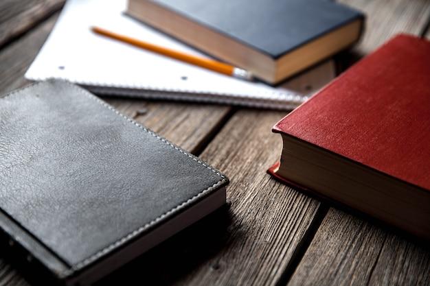 Conceito de negócio, ideias, livros e caderno em uma mesa de madeira com lápis