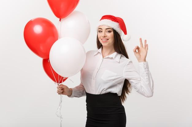 Conceito de negócio - linda jovem mulher de negócios confiante com chapéu de papai noel segurando um balão comemorar o natal.