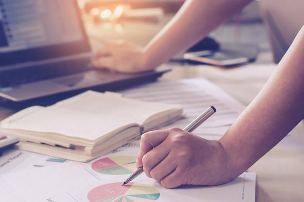 Conceito de negócio: mão de uma mulher usando o laptop e segurando a caneta e apontando papel gráfico busine