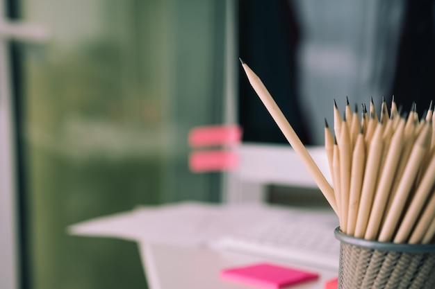 Conceito de negócio - muitos lápis e o lápis são maiores do que o outro no desfoque de fundo.