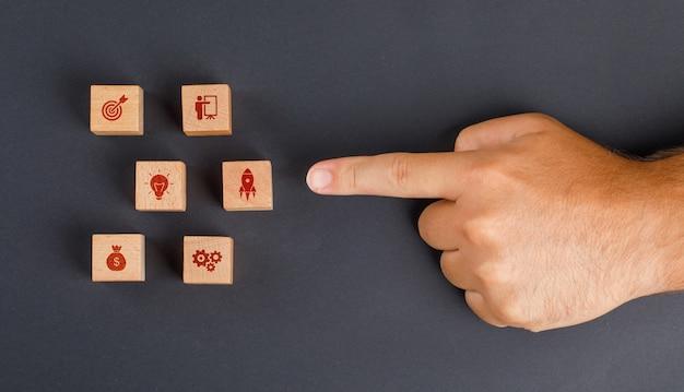 Conceito de negócio na mesa cinza escuro plana leigos. dedo mostrando o cubo de madeira com o ícone.