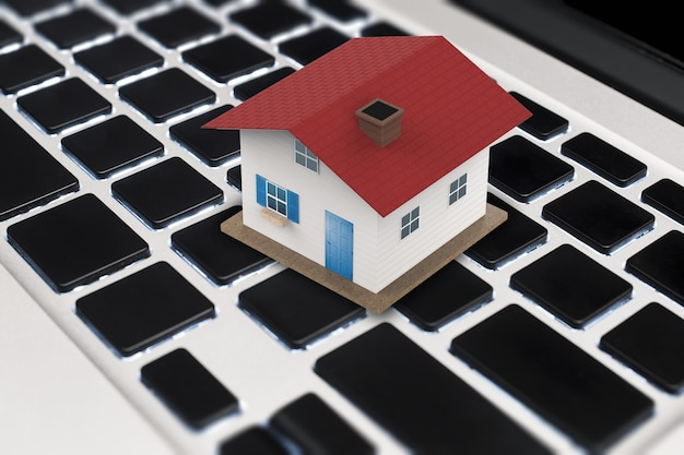 Conceito de negócio online com casa de telhado vermelha simulada no teclado