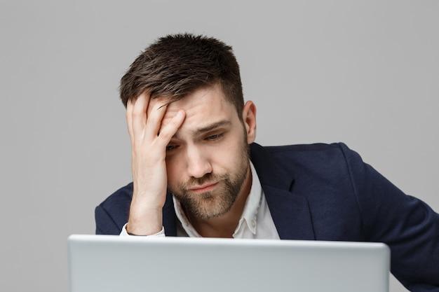 Conceito de negócio - retrato bonito homem de negócios estressante em choque terno olhando para o trabalho no laptop. fundo branco.