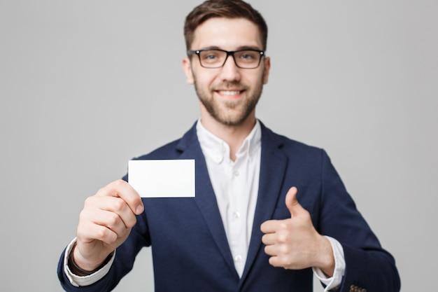 Conceito de negócio - retrato bonito homem de negócios que mostra o cartão de nome com rosto sorridente e confiante. espaço branco. espaço de cópia.