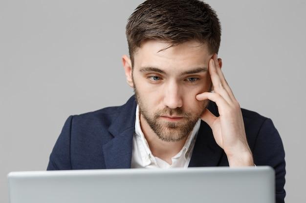 Conceito de negócio - retrato bonito homem de negócios sério em terno olhando para laptop. fundo branco.