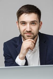 Conceito de negócio - retrato bonito homem de negócios sério em terno olhando para o trabalho no laptop. fundo branco.