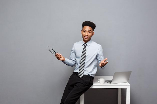 Conceito de negócio - retrato de empresário africano americano com óculos tomando café sentado em uma mesa usando um laptop.