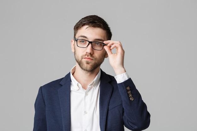 Conceito de negócio - retrato de um empresário bonito em terno com óculos de pensamento sério com expressão facial estressante. fundo branco isolado. espaço de cópia.