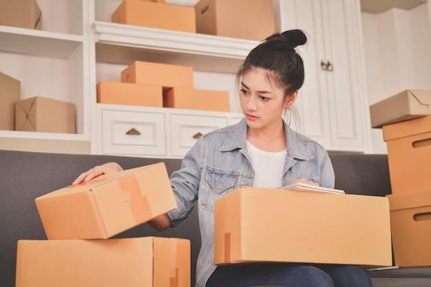 Conceito de negócio sme. os jovens asiáticos estão embalando seus pacotes.