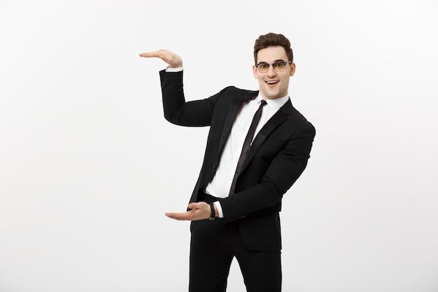 Conceito de negócio - sorriso feliz de homem de negócios jovem e bonito, empresário mostrando algo na palma da mão aberta, conceito de produto de propaganda isolado sobre fundo branco