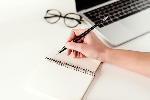 Conceito de negócio - trabalho em um escritório moderno brilhante com um laptop, notebook e óculos
