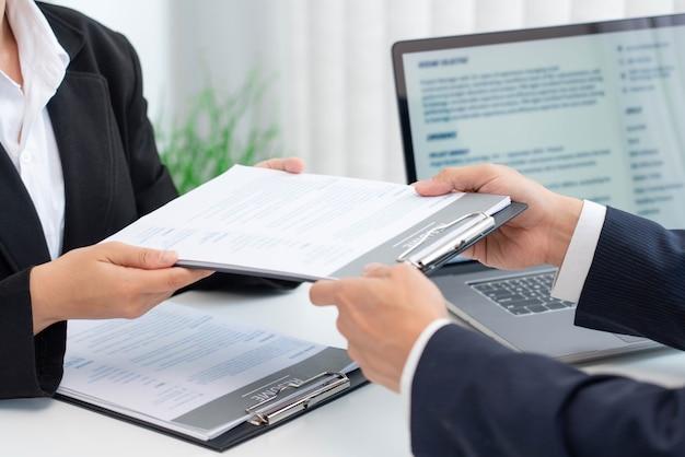 Conceito de negócio: uma candidata entregando o currículo de trabalho com as experiências e formação educacional para os recursos humanos.