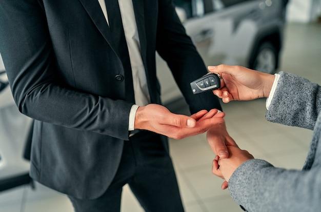 Conceito de negócio, venda de carros, negócio, gesto e pessoas de automóveis - feche do revendedor, dando a chave ao novo proprietário e apertando as mãos em salão de automóveis ou salão de beleza.