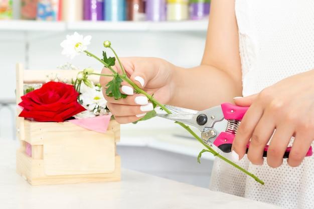 Conceito de negócio, venda e produtos de floricultura - close-up da mulher de florista segurando o monte na loja de flores