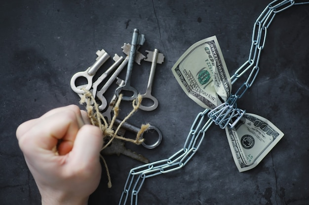 Conceito de negócios. a depreciação da moeda nacional. nota de cem dólares. inflação e estagnação. aperte a nota de cem dólares com uma corrente de medição.
