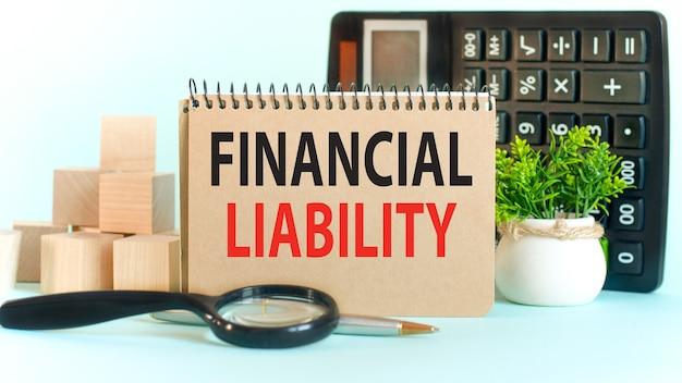 Conceito de negócios. caderno com o texto responsabilidade financeira folha de notas de papel branco, blocos de madeira, caneta, lupa, calculadora