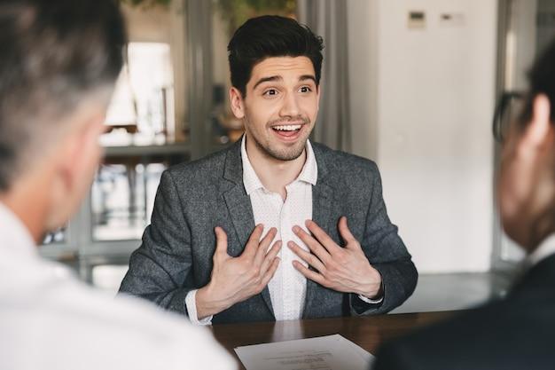 Conceito de negócios, carreira e colocação - homem caucasiano satisfeito dos anos 30 se regozijando e expressando surpresa ao contratar, durante entrevista de emprego com funcionários no escritório