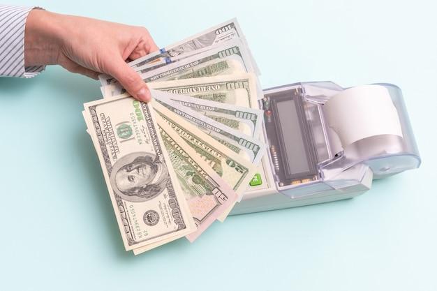 Conceito de negócios. close de uma mão feminina segurando várias notas de centenas de dólares acima da caixa registradora para pagar por um produto ou serviço