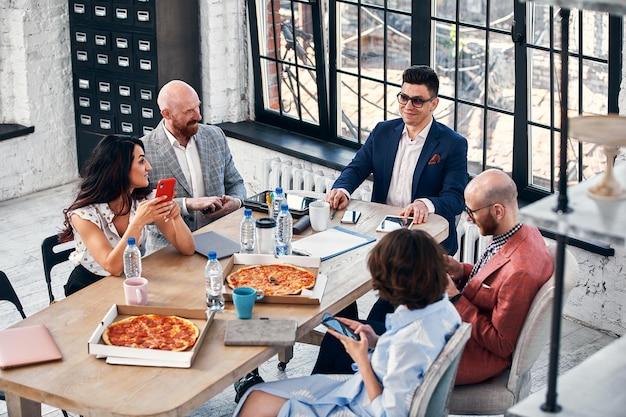 Conceito de negócios, comida, almoço e pessoas - equipe de negócios internacionais feliz comendo pizza no escritório.