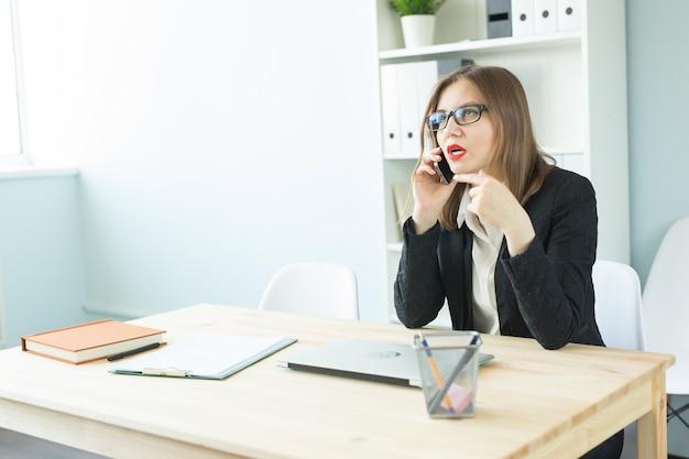 Conceito de negócios, corretor de imóveis e pessoas - mulher atraente no escritório falando ao telefone
