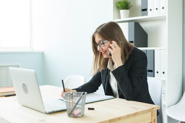 Conceito de negócios, corretor de imóveis e pessoas - mulher atraente no escritório falando no telefone e fazer anotações