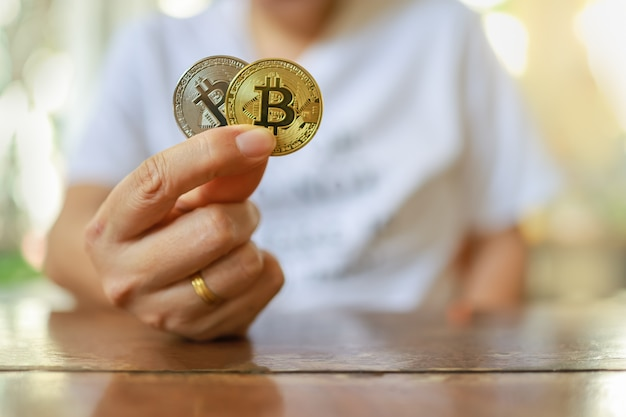 Conceito de negócios, dinheiro, tecnologia e criptomoeda. feche a mão do homem segurando moedas de ouro e prata bitcoin na mesa de madeira.