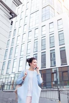 Conceito de negócios e freelance. jovem mulher trabalhando com um telefone celular na rua, com prédios de escritórios ao fundo