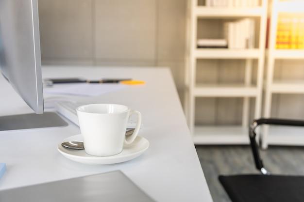 Conceito de negócios e local de trabalho. feche acima da xícara branca de café quente na mesa de trabalho com computador e teclado na sala de trabalho do escritório.