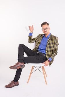 Conceito de negócios e pessoas - homem bonito se senta em sua cadeira e segurando uma xícara no fundo branco.