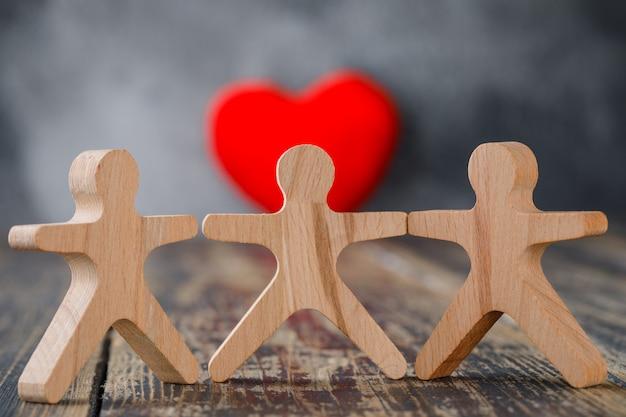 Conceito de negócios e seguros com figuras de madeira de pessoas, close-up coração vermelho.