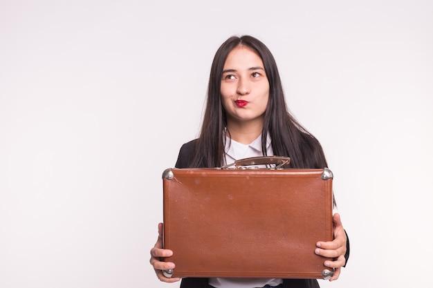 Conceito de negócios, emoções e pessoas - jovem morena mantém uma mala e pensa em uma pergunta na parede branca com espaço de cópia