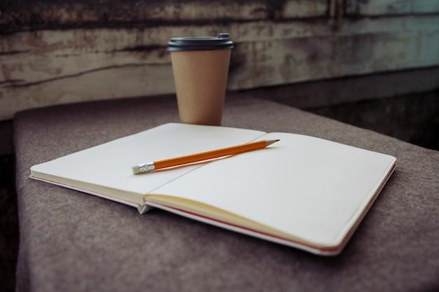 Conceito de negócios, estilo de vida, comida e café - xícara de café de lápis, caderno e papel em um fundo de tecido marrom