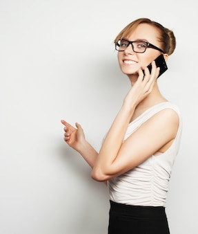 Conceito de negócios, finanças e pessoas: bela jovem empresária segurando um telefone celular, em pé contra um fundo cinza
