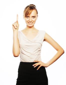 Conceito de negócios, finanças e pessoas: jovem mulher de negócios apontando para um fundo branco.