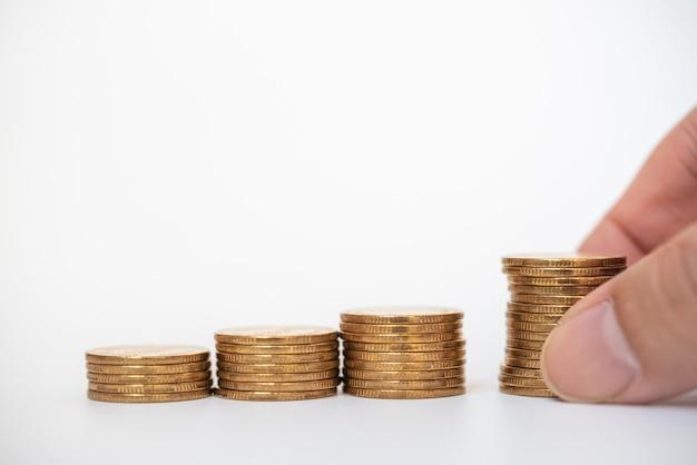 Conceito de negócios, financeiro e de economia. close da pilha de moedas de ouro com o dedo do homem segurando no fundo branco