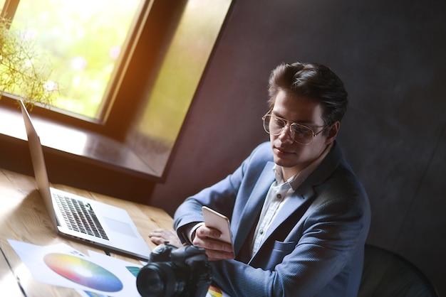 Conceito de negócios, inicialização e pessoas - empresário feliz ou trabalhador de escritório masculino criativo com computador chamando no smartphone