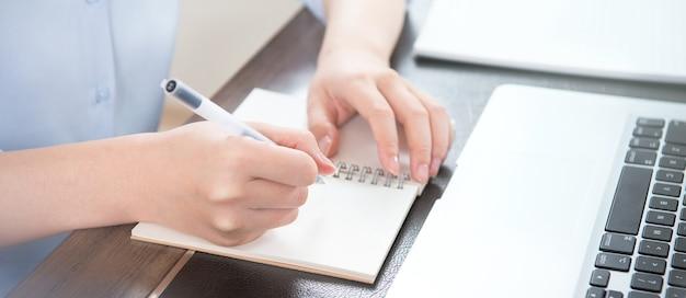 Conceito de negócios. mulher anota o projeto com o laptop e o relatório na mesa do escritório. luz de fundo, efeito de reflexo do sol, close-up, vista lateral, espaço de cópia