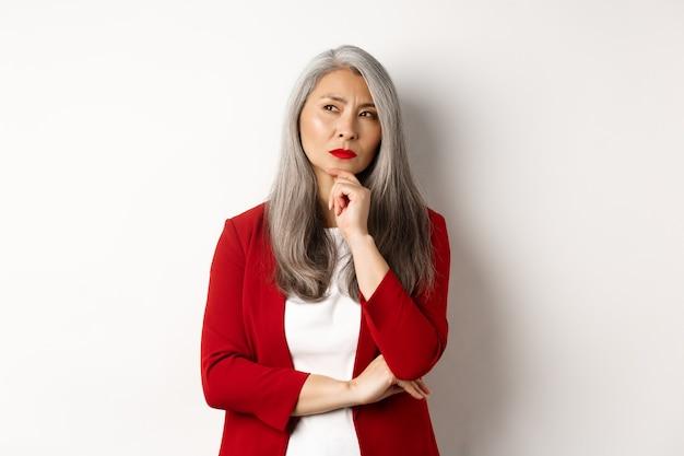 Conceito de negócios. mulher de negócios asiática sênior pensativa olhando para o lado, pensando em pé sobre um fundo branco