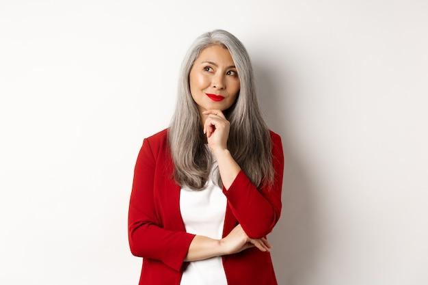 Conceito de negócios. mulher madura sorridente de blazer vermelho, sorrindo e parecendo satisfeita enquanto pensa, em pé sobre um fundo branco