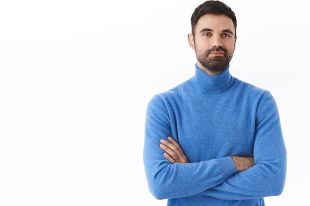 Conceito de negócios, pessoas e estilo de vida. retrato de um homem bonito e confiante com barba, braços cruzados no peito, parece orgulhoso, sente-se como um profissional, recomendo entrar em contato com sua empresa se houver problemas